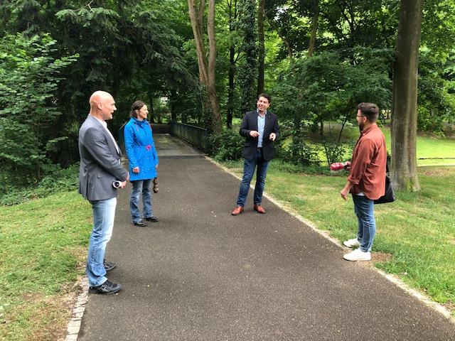 Thomas Hitschler auf einem Parkweg mit drei Menschen im Gespräch.