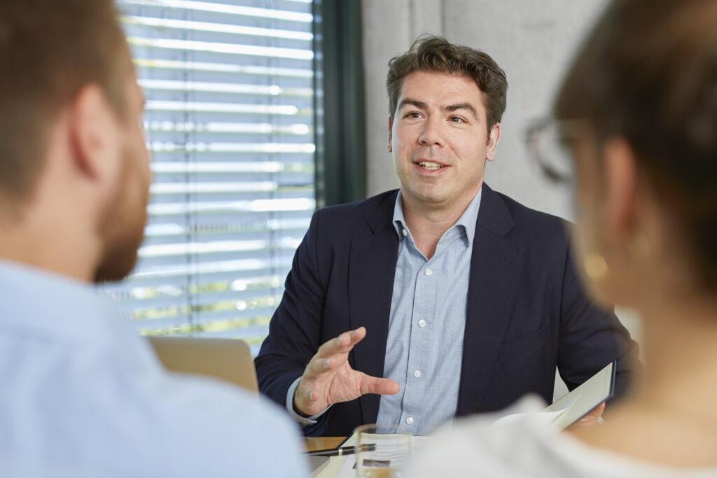 Thomas Hitschler in einem Büro mit Mappe vor sich liegend im Gespräch mit zwei jungen Menschen.